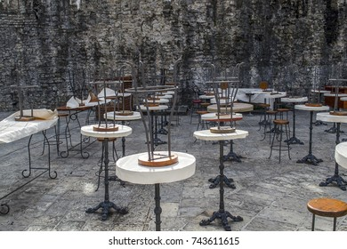 Tables and chairs of a street cafe without people against a rough stone wall.