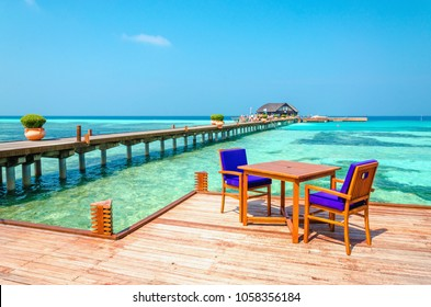 Tables and chairs in a wooden restaurant on stilts on the background of azure water and sunny blue sky