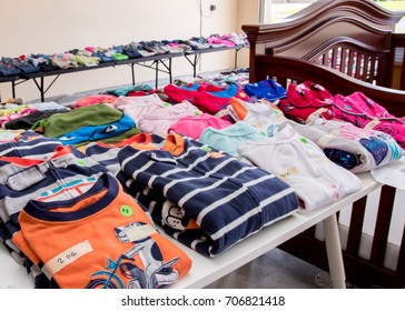 Tables of clothing and baby goods arranged at a suburban garage sale