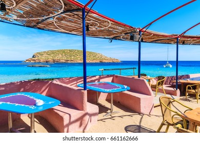Tables in coastal restaurant on Cala Comte beach, Ibiza island, Spain