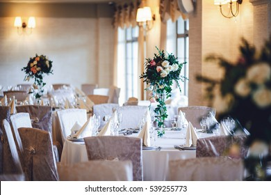 Tables covered with beige cloth and decorated with white rose bouquets