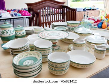 Tables of dishes and baby goods at a suburban garage sale