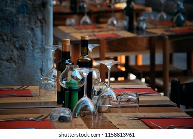 Tables and glass cups waiting for guests in street in Venice, Italy.