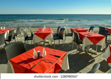 Tables of an outdoor restaurant by the beach with the sea on the background, Alassio, Liguria, Italy