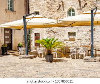 Tables in the restaurant in the open air. Ancient stone buildings on the streets of Split in Croatia.