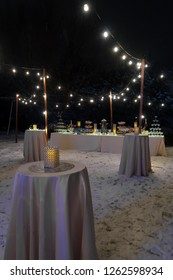 Tables set up for an outdoor evening party. Night time.