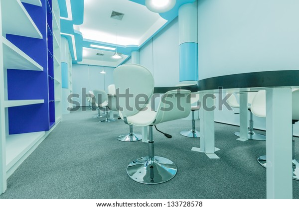 tables and white chairs in the empty modern library