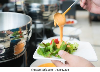 Tablespoon measure of creamy thousand island dressing being poured over fresh garden salad in breakfast buffet at hotel