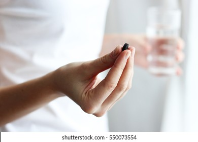 tablet of activated charcoal and a glass of water in female hands. The concept of health