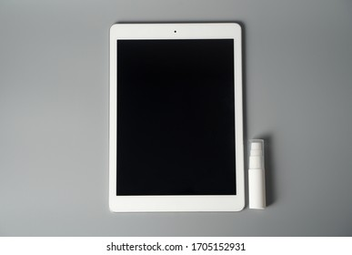 Tablet, alcohol solution, on a gray background. The concept of protecting and disinfecting the workspace from viruses and bacteria. For your design.