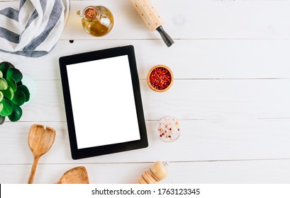 Tablet with blank screen and different kitchen and cooking utensils on whie wooden table. Culinary blog, recipe template, online cooking courses. Top view with copy space. Flat lay