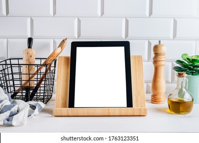 Tablet with blank screen and different kitchen and cooking utensils on whie wooden table. Culinary blog, recipe template, online cooking courses. Selective focus