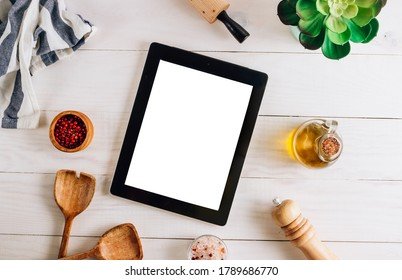 Tablet with blank screen and different kitchen and cooking utensils on whie wooden table. Culinary blog, recipe template, online cooking courses. Top view. Flat lay