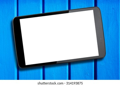Tablet with blank white screen displayed towards the camera on light blue wooden table