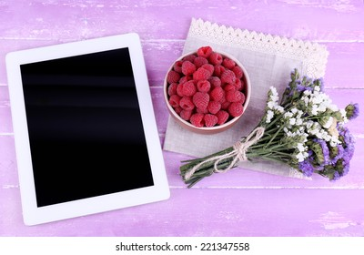 Tablet,, bowl of raspberries and bunch of wildflowers on napkin on wooden background