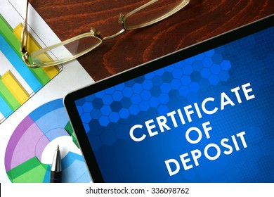 Tablet with certificate of deposit (CD) on a table. Business concept.
