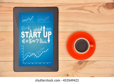 tablet  and coffee with start up scheme on table, above view