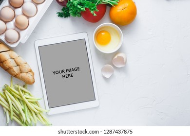 Tablet computer with fresh vegetables on white background, copy space