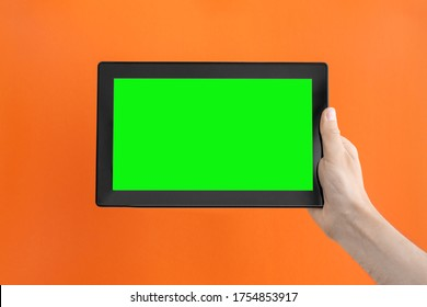 Tablet computer with green screen in man's right hand on an orange background.