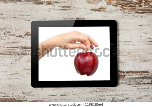 Tablet computer with the hand and a red apple on the screen on a background of wood