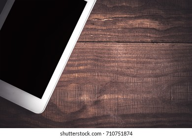 Tablet computer mock-up on a wooden table. Close up, top view. Copy space
