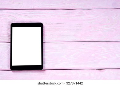 Tablet computer on pink wooden boards. White screen. Top view.