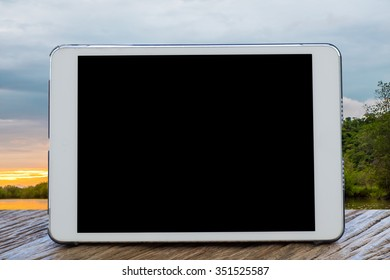 Tablet Computer on table with blurred sea sunset background.