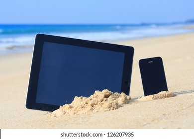 tablet computer and smartphone on the beach.