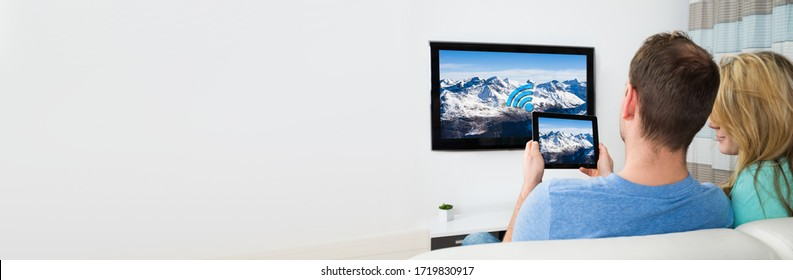 Tablet Connected To TV. People Watching And Streaming