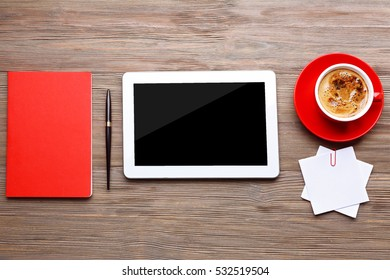 Tablet with cup of coffee and office tools on wooden background
