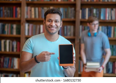 Tablet. Dark-haired young latino in a blue tshirt showing his tablet