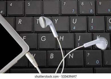 tablet earphones on keyboard