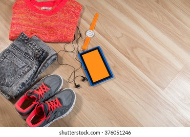 tablet with earphones, watch, clothing and sneakers on the wooden background