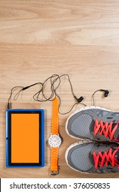 tablet with earphones, watch and sneakers on the wooden background