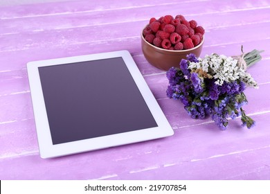 Tablet, field flowers and bowl of raspberries on wooden background