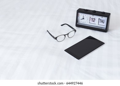 Tablet glasses, alarm clock on the bed