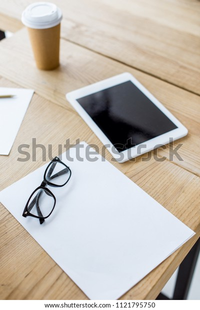 tablet and glasses on wooden table in business office