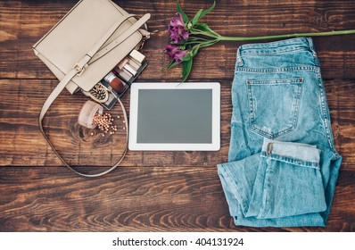 tablet and golden bag with cosmetics fashion denim jeans and blooming flower on wooden background note