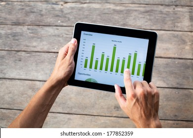 tablet with green chart in hands of business man