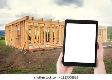 Tablet in the hands of Mrs. architect during a control visit. Construction of a wooden house, isolated blank screen with copy space.