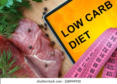 Tablet with low carb diet and fresh meat  on wooden board