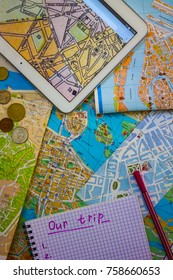 Tablet with a map of Paris, maps of European cities. A simple Notepad and pen, some coins. Develop travel itinerary, independent tourism. The view from the top.