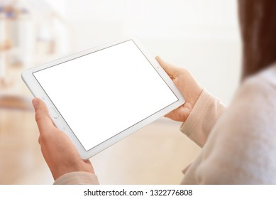 Tablet mockup closeup. White tablet in woman hands. room and sunlight in background.