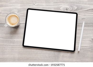 Tablet mockup with empty white screen and wireless stylus pen on table