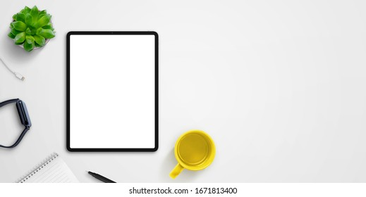 Tablet mockup on desk surrounded by watch, coffee mug, pad, plant and pen. Copy space beside for text