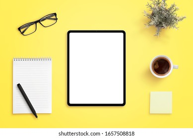 Tablet mockup on yellow office desk. Isolated screen for app or web site design promotion. Pad, pen, cup of coffee, glasses and plant beside