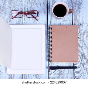 Tablet, mug of coffee, notebook, glasses and pens on wooden background