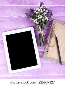 Tablet, notebook, pencil and bunch of field flowers on wooden background