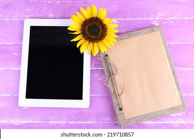 Tablet, notebook and sunflower on wooden background
