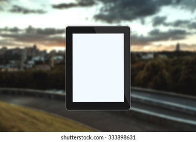 tablet on blurred landscape
